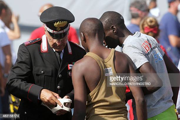 A Carabinieri military police officer give sandals to migrants after they disembarked from the Irish military vessel Naimh after its arrival in the...
