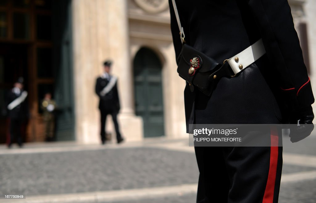 Carabinieri patrol Montecitorio Square at the Parliament in Rome on April 28, 2013 the day after a Carabiniere police officer was shot by an apparently disturbed man outside the Italian Prime minister offices, while the country's new ministers were being sworn in . Italian newly appointed Prime Minister Enrico Letta, a 46-year-old moderate from the centre-left Democratic Party, unveils his coalition government's programme prior to a vote of confidence in the lower house today. AFP PHOTO / FILIPPO MONTEFORTE