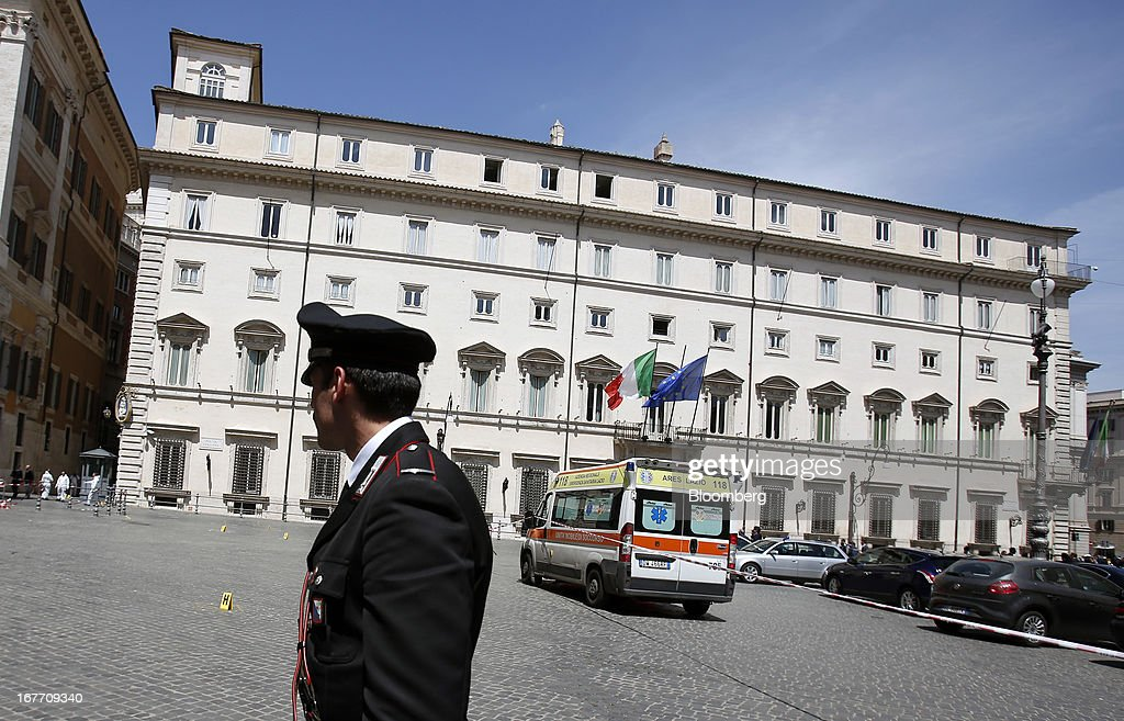 A Carabinieri police officer stands on duty near an ambulance following a shooting outside the Chigi Palace in Rome, Italy, on Sunday, April 28, 2013. Two Italian police officers were shot outside the prime minister's office in Rome today by a lone gunman while the country's new premier, Enrico Letta, was being sworn in across town, police said. Photographer: Alessia Pierdomenico/Bloomberg via Getty Images