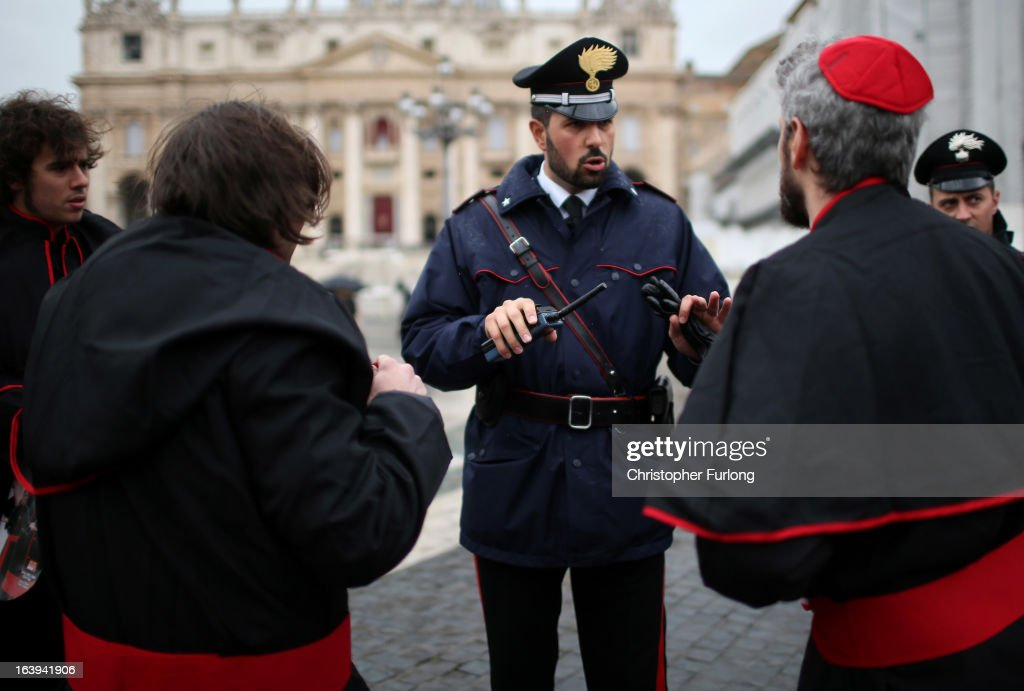 Carabinieri police officers intervene as men dress up in fake cardinal gowns in St Peter's Square as workers prepare for the inauguration mass of pope Francis on March 18, 2013 in Vatican City, Vatican. The Inauguration Mass for Pope Francis will take place on March 19, the feast day for St. Joseph.