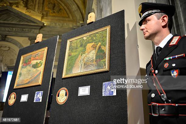 A Carabinieri stands next to the two paintings stolen in London in the 1970s by French artists Paul Gauguin 'Fruits sur une table ou nature morte au...