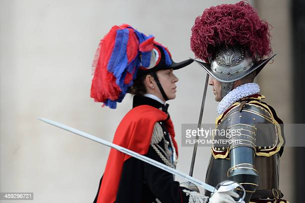 A carabinieri walks past a Swiss guard at St Peter's square before Pope Francis' traditional Christmas 'Urbi et Orbi' blessing from the balcony of St...