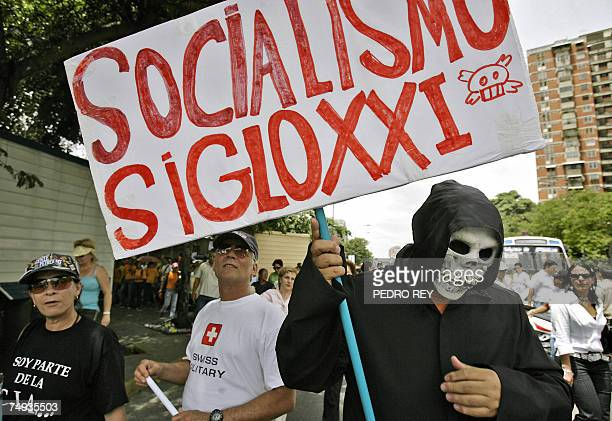 A man representing 'The Death' and holding a poster reading 'Socialism XXI Century' marchs along with journalists during the National Journalist Day...