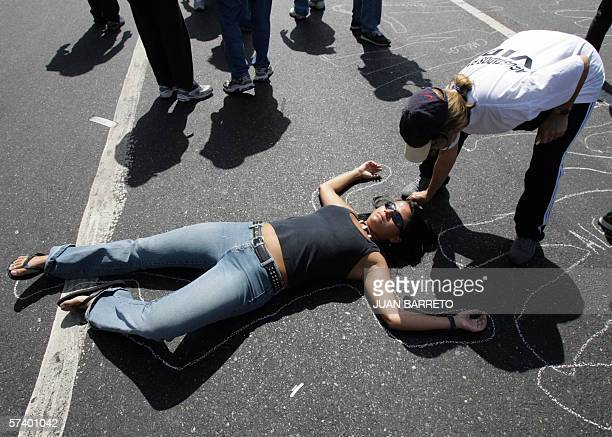 A protester lies down on the tarmac mocking to be dead during a massive rally 22 April 2006 in Caracas Thousands of Venezuelans marched Saturday...