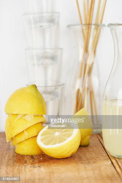 Carafe of lemon juice, glasses, sliced and squeezed lemons on wood