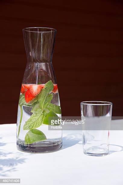 A carafe of water with sliced strawberries and mint leaves