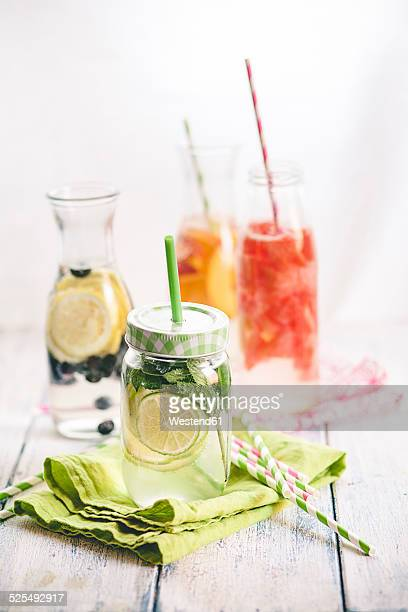 Carafes of miscellaneous fruit infused water on cloth and wood