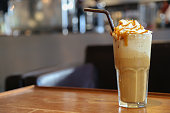 Caramel frappe coffee on brown wood table with space in the coffee shop.