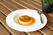 Caramel custard cake with peppermint leaf in white plate on wooden table.