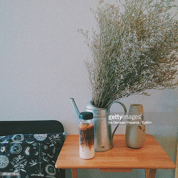 Caramel Macchiato And Flower Pot On Table Against Wall