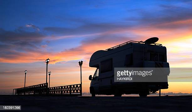 Caravan on the road and bridge at sunset