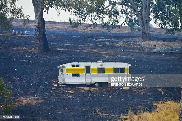A caravan saved from the fire sits on charred earth near One Tree Hill in the Adelaide Hills northeast of Adelaide on January 3 2015 Houses were lost...