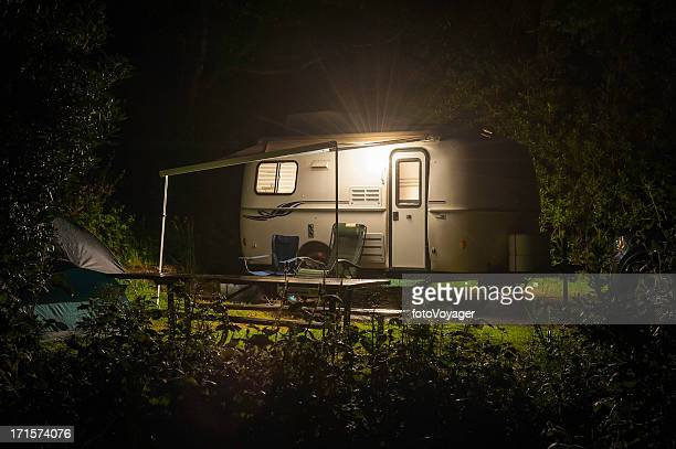 Caravan trailer glowing in forest camp site night