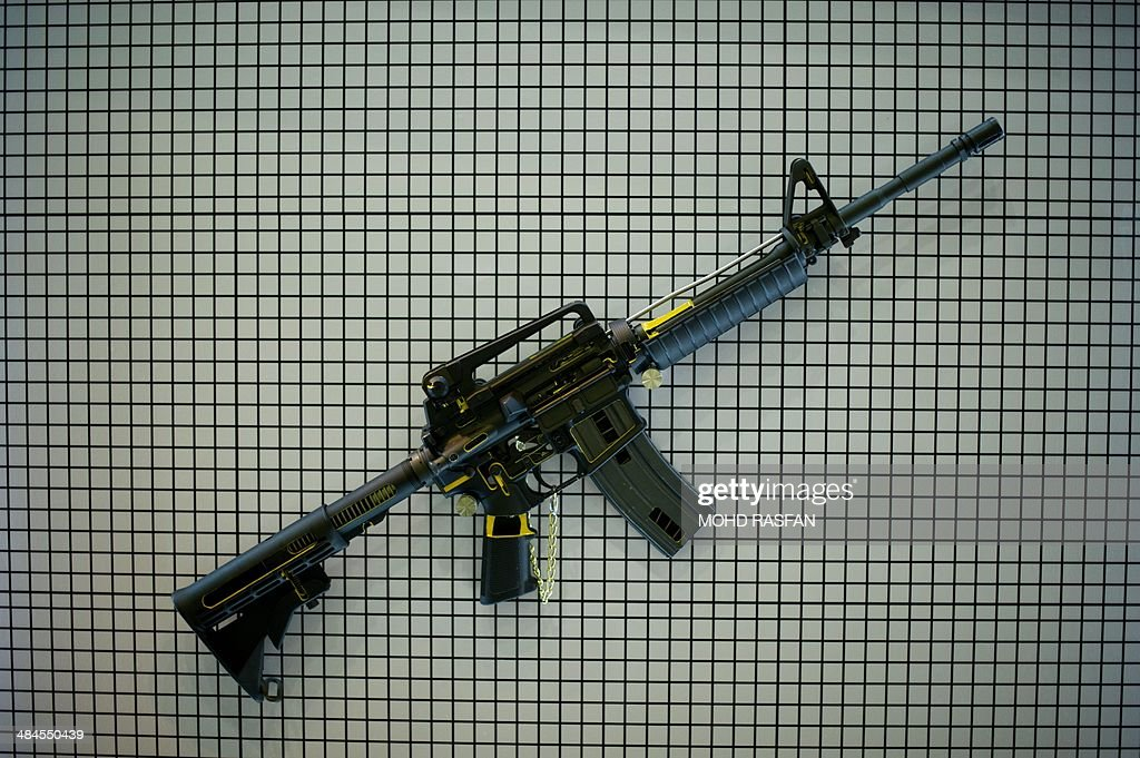 Carbine assault rifle hangs on a wall during preparations for the 14th Defence Services Asia Exhibition and Conference at the Putra World Trade...