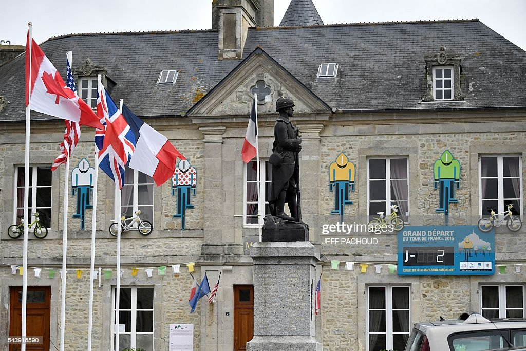 Carboard silhouettes shaped as cyclists wearing the Tour de France's colors of jersey are installed on the facade of the city hall of in Sainte-Marie-du-Mont, Normandy, on July 30, 2016, two days before the start of the 103rd edition of the Tour de France cycling race. The 2016 Tour de France will start on July 2 in the streets of Le Mont-Saint-Michel and ends on July 24, 2016 down the Champs-Elysees in Paris. / AFP / jeff pachoud