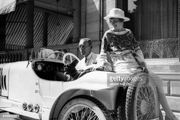 carcompetition in BadenBaden Otto Hoffmann with dog sitting in his Presto car next to him his wife Photographer Atelier Binder Published by 'Die...