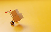 Card boxes on a hand truck on yellow background.  Horizontal composition with selective focus and copy space.