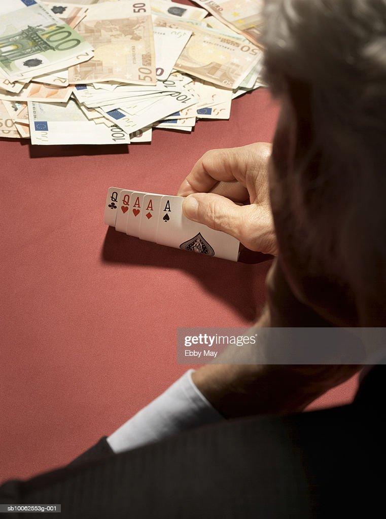 Card player looking at cards, rear view, high angle view, focus on hand and cards : Stock Photo