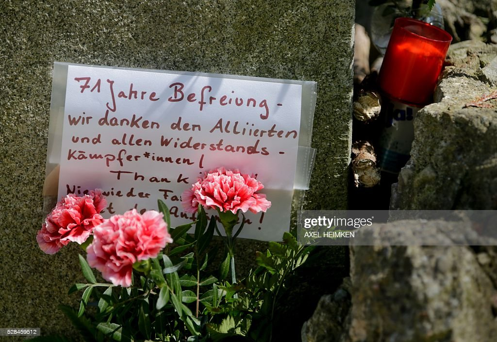 A card reading '71 years of liberation - we thank the Allies and all resistance fighters' is placed along with flowers and a candle next to a memorial stone at the former 'Arbeitserziehungslager Nordmark' labour camp in Kiel, northern Germany, where citizens of Kiel and relatives of former concentration camp prisoners who took part in a death march from Hamburg to Kiel at the end of World War II commemorated the camp's victims on May 5, 2016. The event took place in line with the 'March of the Living', an annual educational program including a march from the Nazi concentration camp Auschwitz to Birkenau in remembrance of the victims of the Holocaust. / AFP / dpa / Axel Heimken / Germany OUT