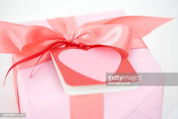 Card with heart graphic atop gift with pink bow, elevated view