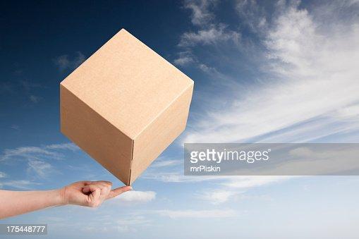 Cardboard box balancing on fingertip