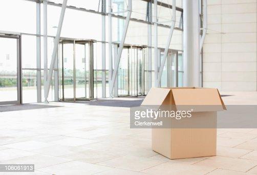Cardboard box lying at a spacious office lobby : Stock Photo