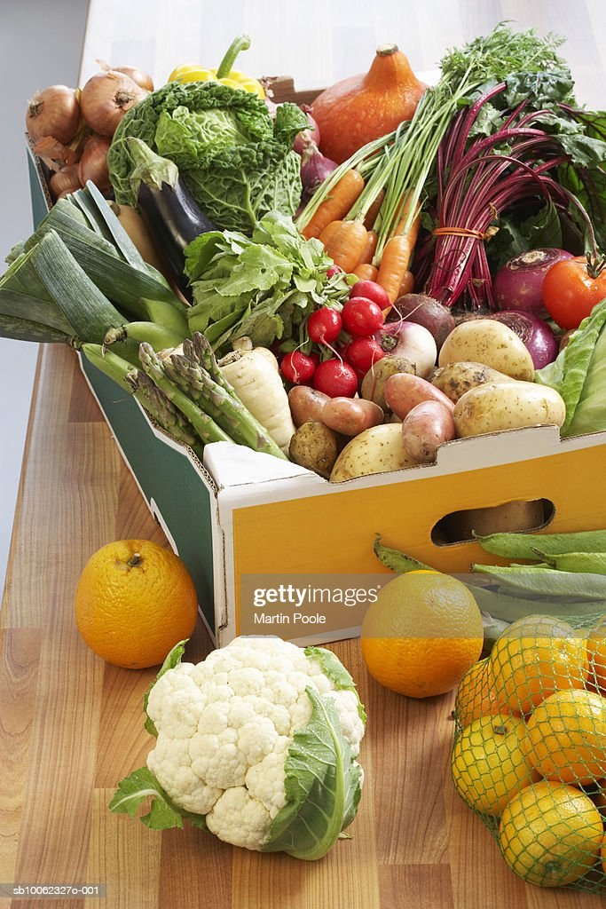 Cardboard box of assorted vegetables on kitchen counter : Stock Photo
