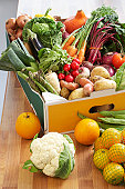 Cardboard box of assorted vegetables on kitchen counter