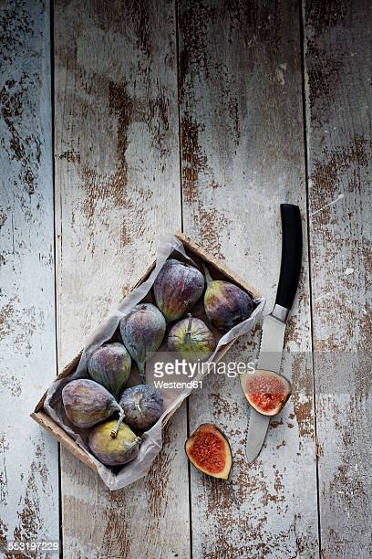 Cardboard box of figs and knife on wood