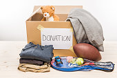 cardboard box with donation clothes and different objects on white, donation concept