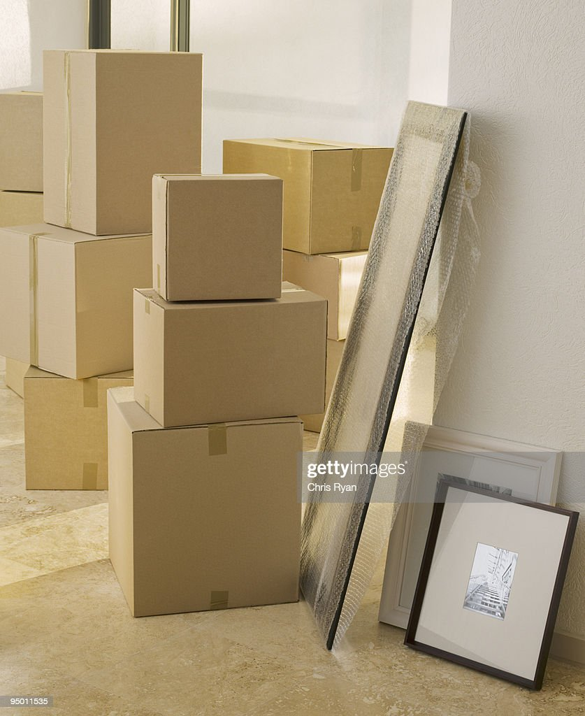 Cardboard boxes and pictures in new house : Stock Photo