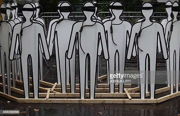 Cardboard cut outs made to resemble humans stand with nooses and blind folds as demonstrators protest Iranian President Hassan Rouhani outside the...