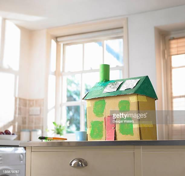 Cardboard house on kitchen work top.