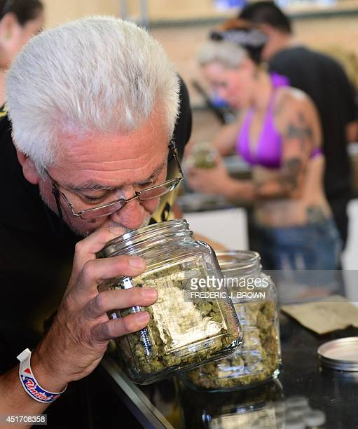 A cardcarrying medical marijuana patient has a sniff of the buds in glass jars on display at Los Angeles' firstever cannabis farmer's market at the...