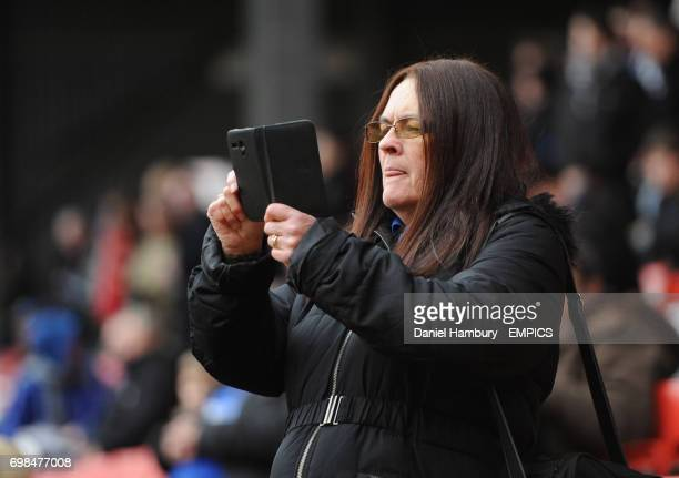 A Cardiff City fan takes pictures with her smart phone in the stands