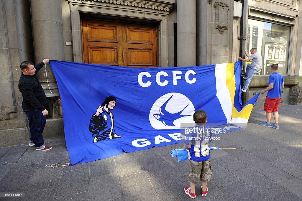 Cardiff City fans attach a banner to a building on St. Mary's Street during the Cardiff City FC victory parade in honour of the football club winning the npower Championship League trophy on May 05, 2013 in Cardiff, Wales.