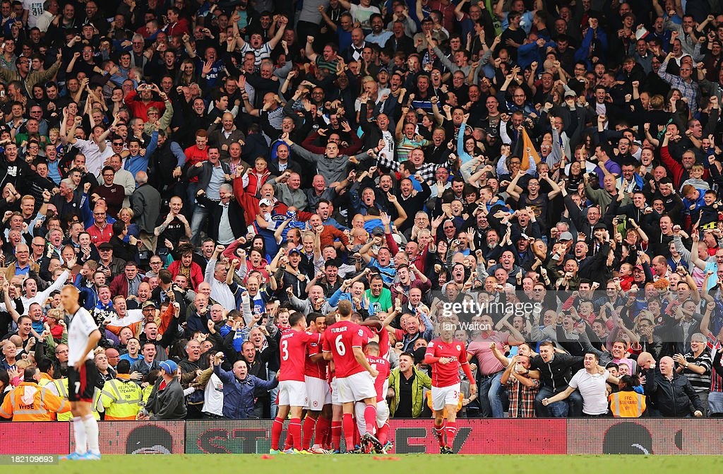 Cardiff City fans celebrate Jordon Mutch's winning goal during the Barclays Premier League match between Fulham and Cardiff City at Craven Cottage on September 28, 2013 in London, England.