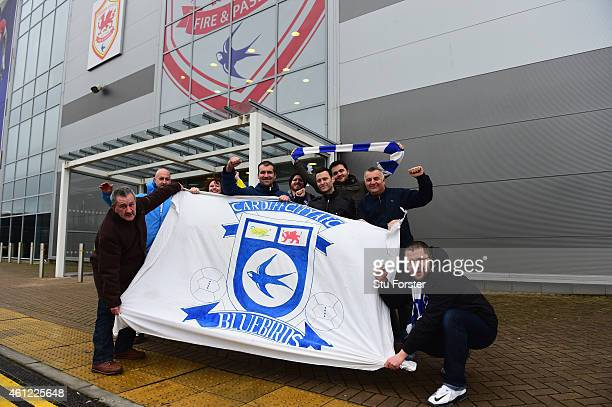 Cardiff City fans pose outside the ground after it was announced at a press conference that the club would revert to their blue home kit from red...