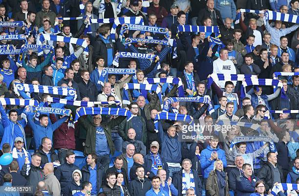 Cardiff City fans wave their former colours in a demonstration against owner Vincent Tan during the Barclays Premier League match between Cardiff...