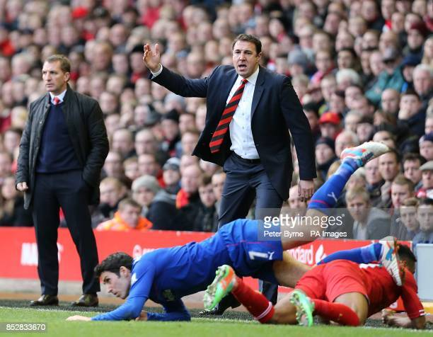 Cardiff City manager Malky Mackay looks on as his player Peter Whittingham collides with Liverpool's Raheem Sterling