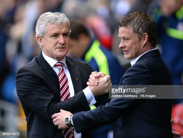 Cardiff City manager Ole Gunnar Solskjaer shakes hands with Stoke City manager Mark Hughes before the Barclays Premier League match at the Cardiff...