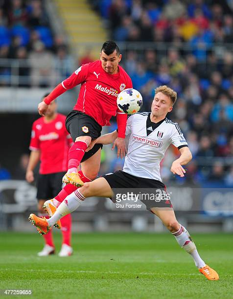 Cardiff City player Gary Medel challenges Cauley Woodrow of Fulham during the Barclays Premier league match between Cardiff City and Fulham at...