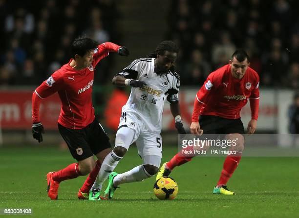 Cardiff City's Gary Medel and BoKyung Kim battle for the ball with Swansea City's Marvin Emnes
