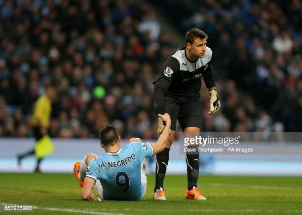 Cardiff City's goalkeeper David Marshall helps up Manchester City's Alvaro Negredo
