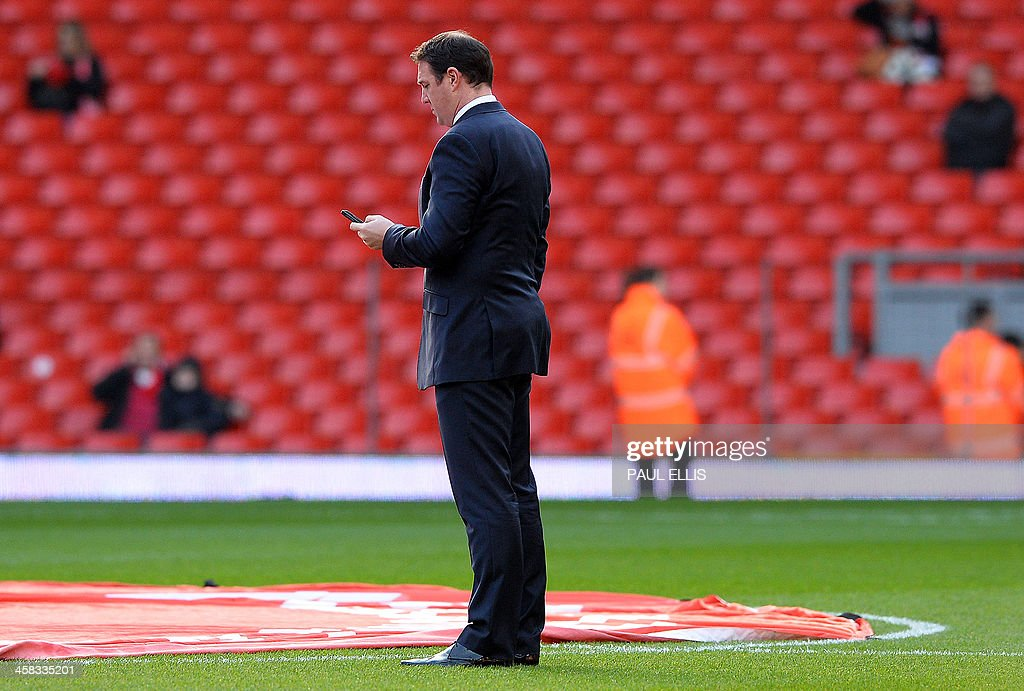 Cardiff City's Scottish manager Malky Mackay looks at his mobile phone before the start of the English Premier League football match between Liverpool and Cardiff City at Anfield stadium in Liverpool, northwest England, on December 21, 2013. AFP PHOTO / PAUL ELLIS USE. No use with unauthorized audio, video, data, fixture lists, club/league logos or live services. Online in-match use limited to 45 images, no video emulation. No use in betting, games or single club/league/player publications.