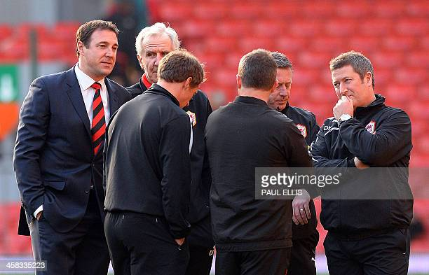 Cardiff City's Scottish manager Malky Mackay talks to his coaching staff before the start of the English Premier League football match between...