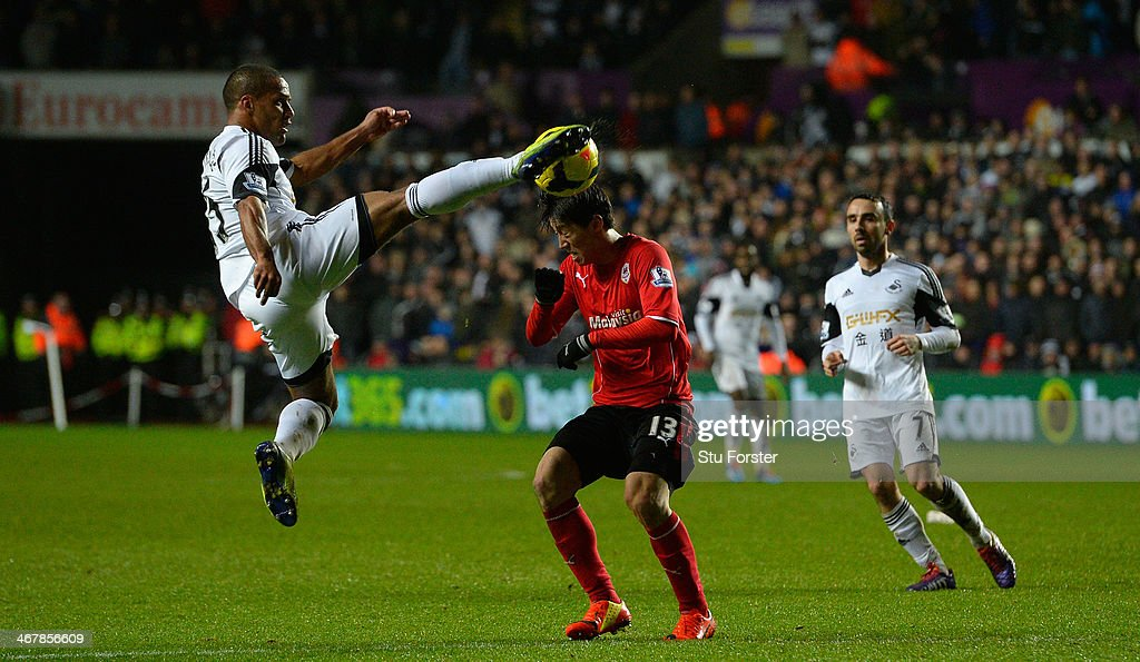Cardiff player Kim Bo- Kyung (c) is challenged by Wayne Routledge (l) during the Barclays Premier League match between Swansea City and Cardiff City at Liberty Stadium on February 8, 2014 in Swansea, Wales.