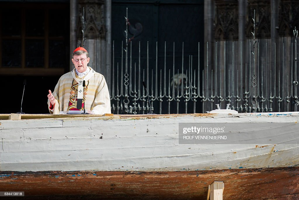 Cardinal and archishop Rainer Maria Woelki conducts the Corpus Christi Mass from a seven-meter-long refugee boat on May 26, 2016 in front of the cathedral in Cologne. Archbishop of Cologne, Cardinal Woelki celebrated the Corpus Christi Mass at the boat in memory of thousands of migrants who lost their lives in the Mediterranean sea. / AFP / dpa / Rolf Vennenbernd / Germany OUT