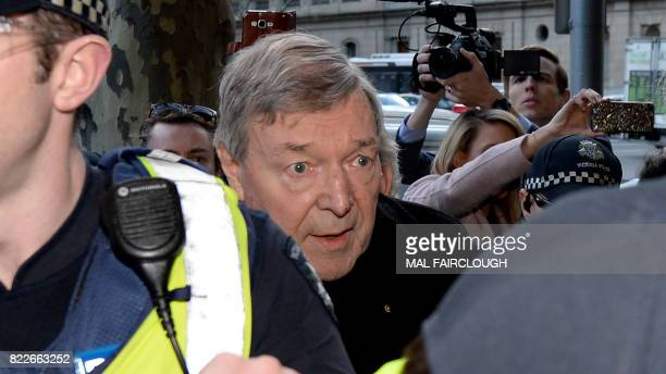 Cardinal George Pell arrives under heavy police protection for a filing hearing at the Melbourne Magistrates Court after being charged with sexual...