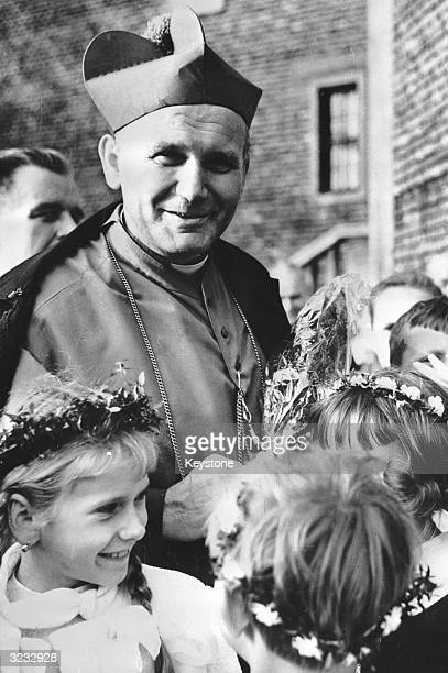 Cardinal Karol Wojtyla later Pope John Paul II is surrounded by little girls during a visit to a village near Krakow